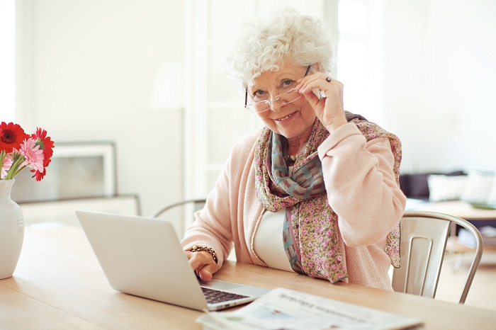 Portrait of a mature woman with laptop smiling at you