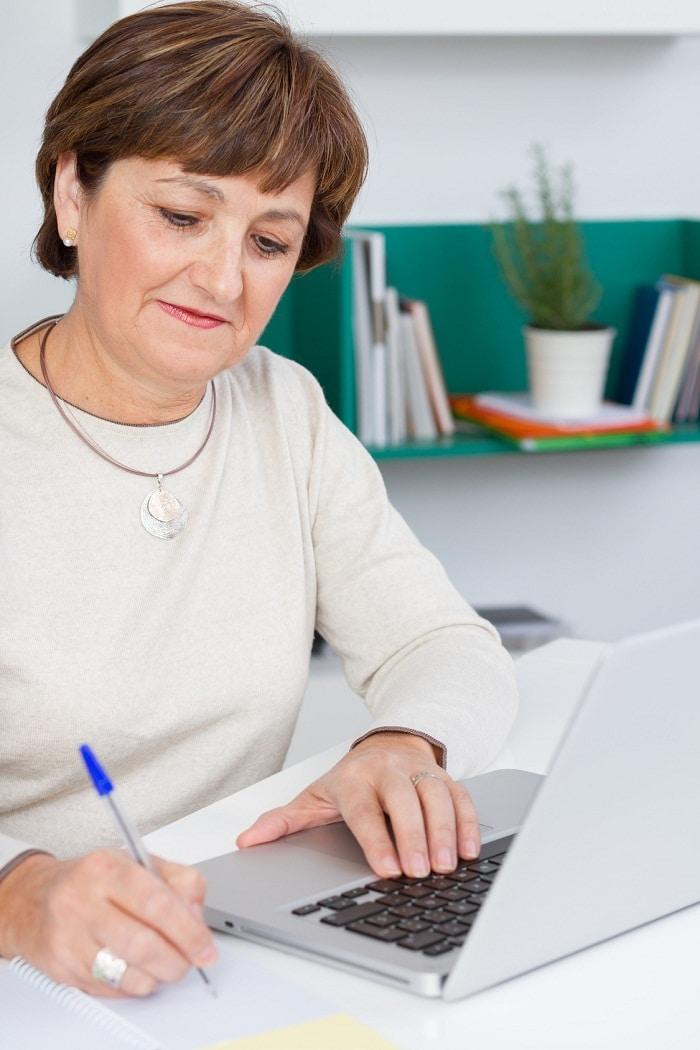 Senior woman taking notes with laptop