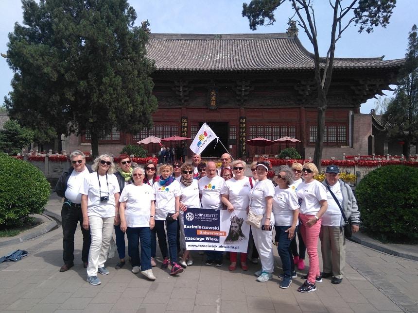 Grupa seniorów KUTW z banerem uczelni przed świątynią Pingyao