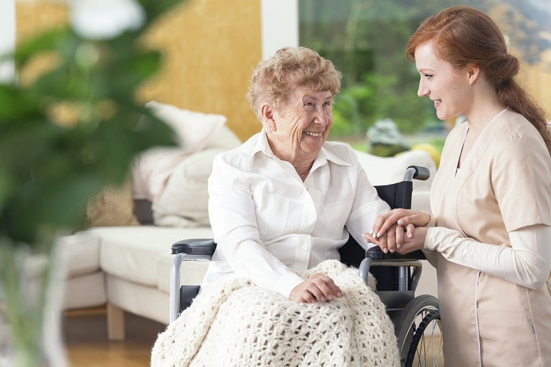 Smiling grandmother on the wheelchair and friendly nurse