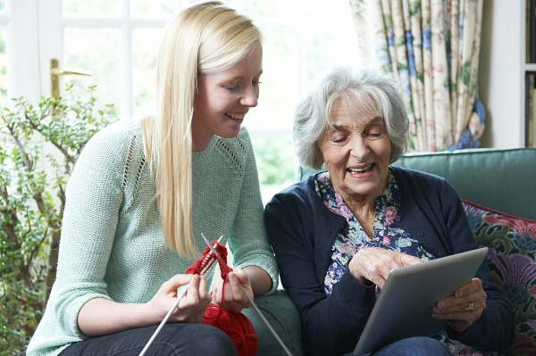 Grandmother Using Digital Tablet As Granddaughter Knits