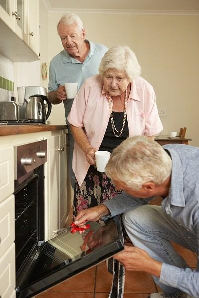 Repairman Fixing Cooker In Senior Couple's Kitchen