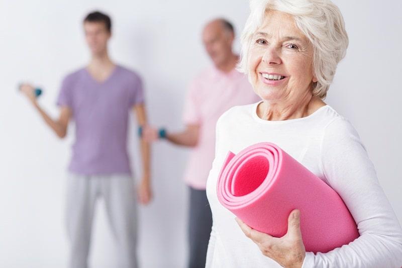 Happy elderly woman at gym