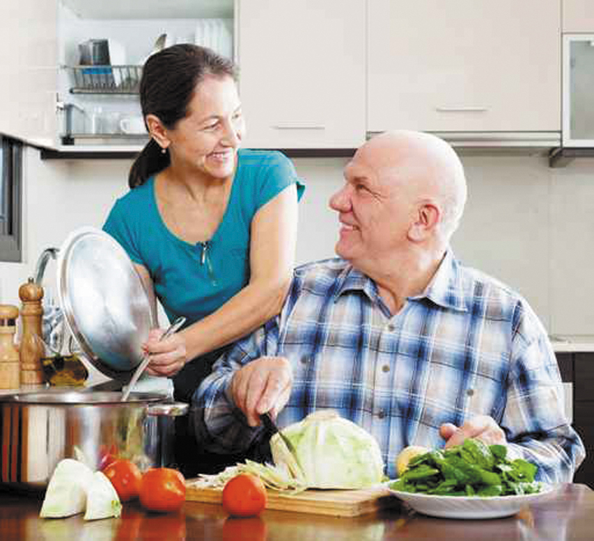 senior couple cooking vegetarian lunch