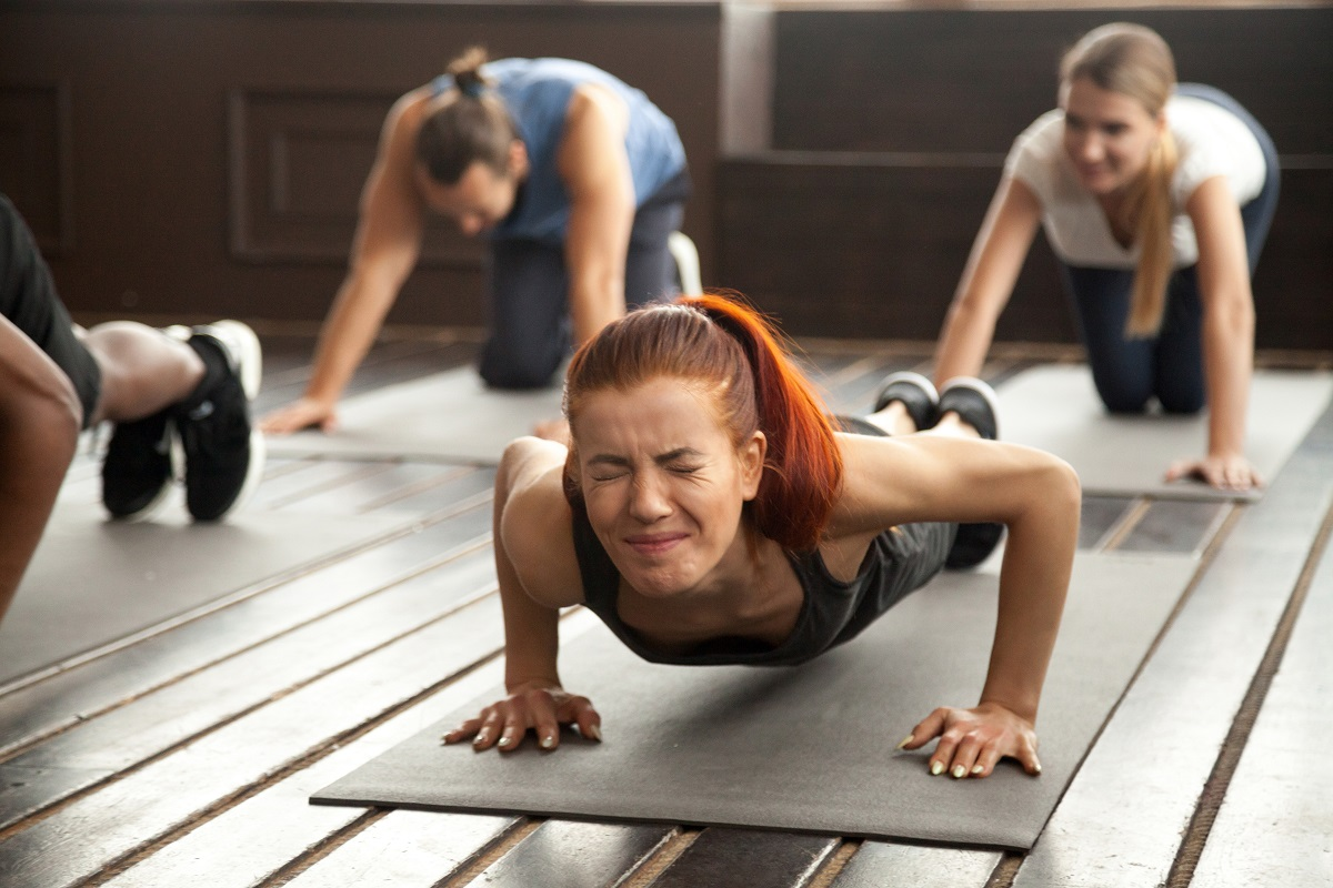 Woman doing difficult plank exercise or pushups at group trainin