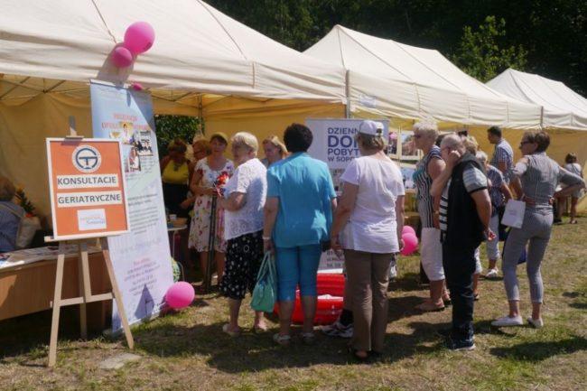 Stoiska z ofertami i poradami dla seniorów podczas festynu na boisku przy Domu Pomocy Społecznej w Sopocie
