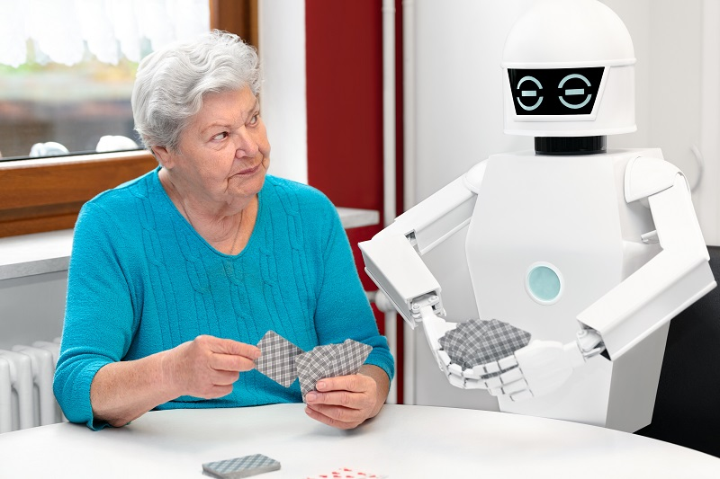 ambient assisted living service robot is playing a card game with a senior adult woman