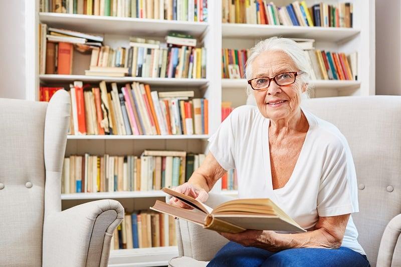 Neugierige Seniorin in der Bücherei liest ein Buch
