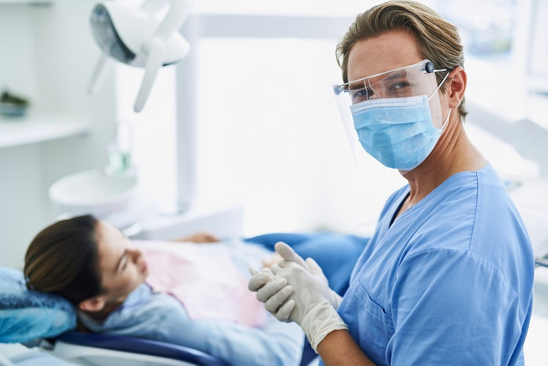Handsome dentist in protective mask feeling satisfied after dental procedure
