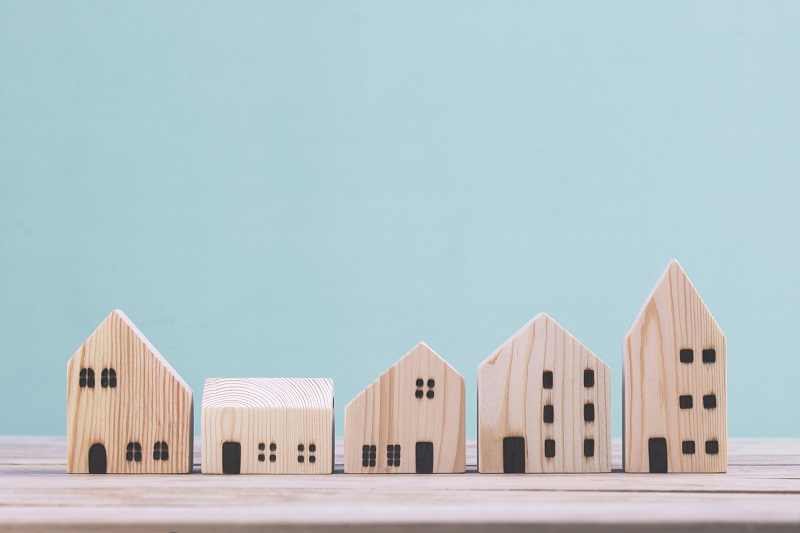 Building different wood house model on blue background , managing property investment concept