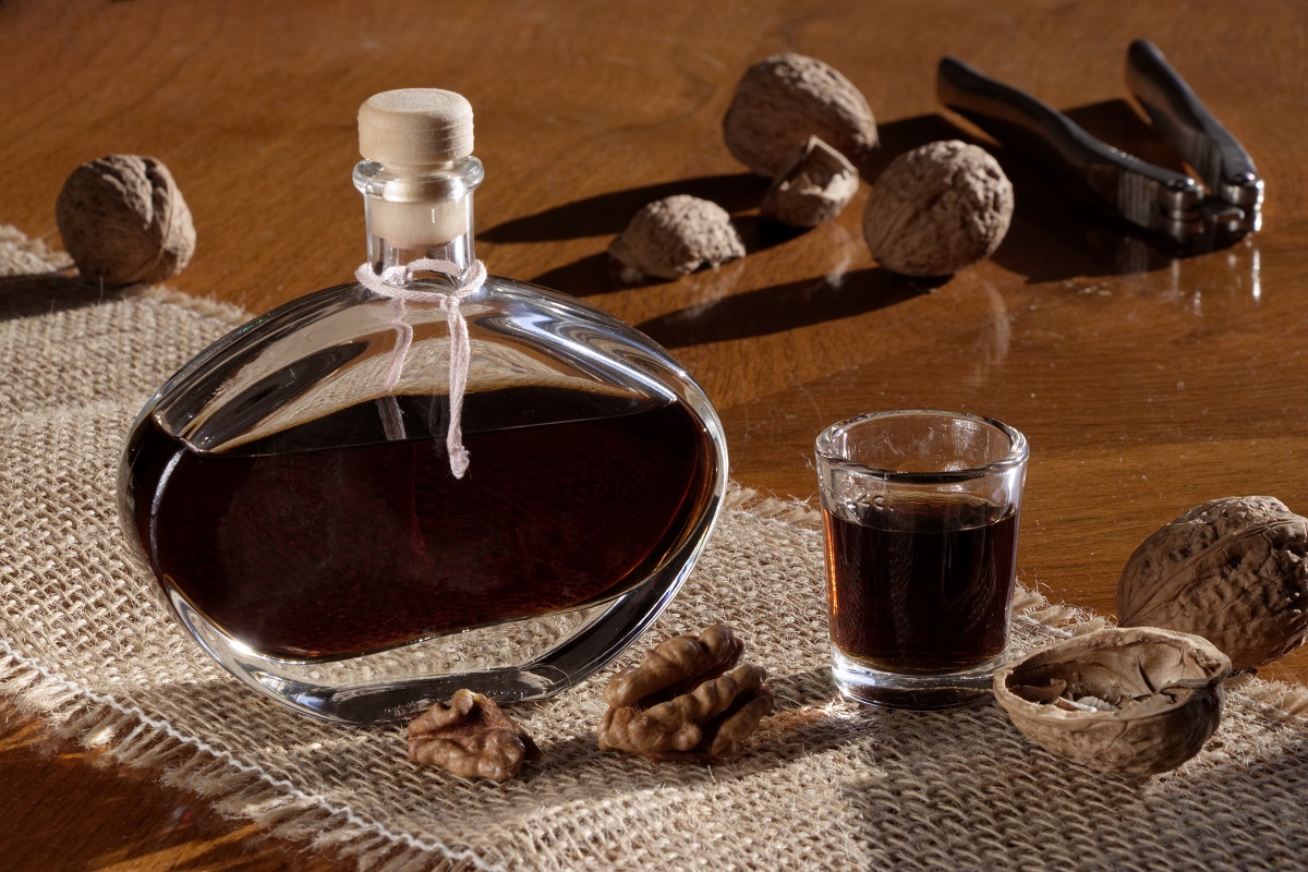 Walnut liqueur in a bottle and shot glass on a wooden table with scattered walnuts