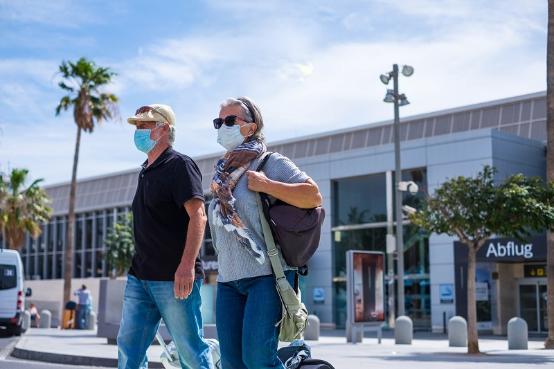 two senior walking with their baggage and wearing medical mask to prevent covid-19 or coronavirus or another type of virus or disease – safe travelers concept and lifestyle walking outdoor