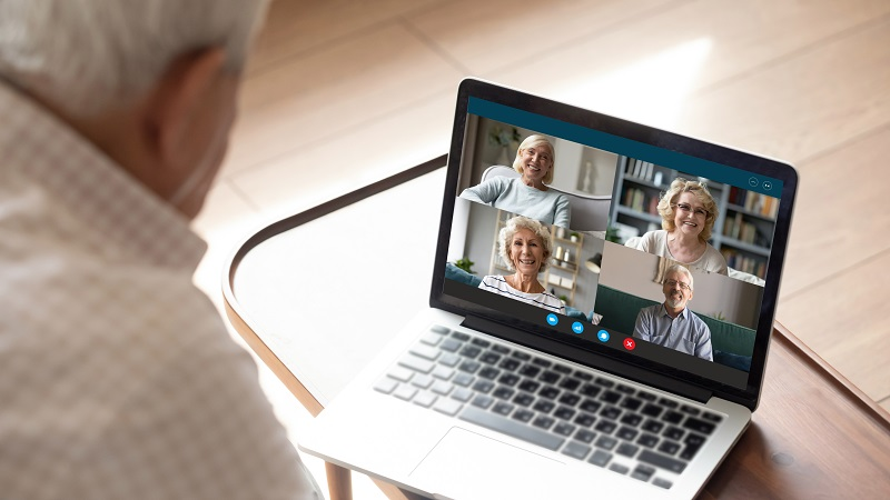 Senior man makes videocall talking with friends by videoconference application