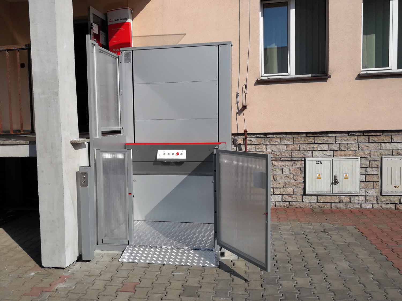 Strzyzow-podnosnik-pionowy-Kali-B-przed-budynkiem-dolny-przystanek-otwarta-furtka