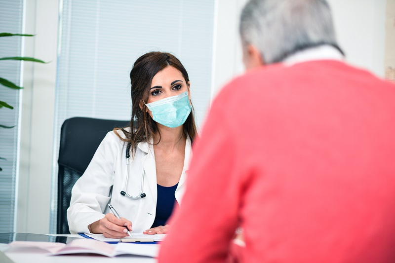 Masked doctor listening to a patient