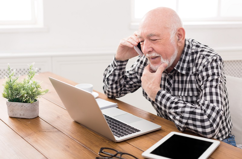Senior man talking on phone with laptop