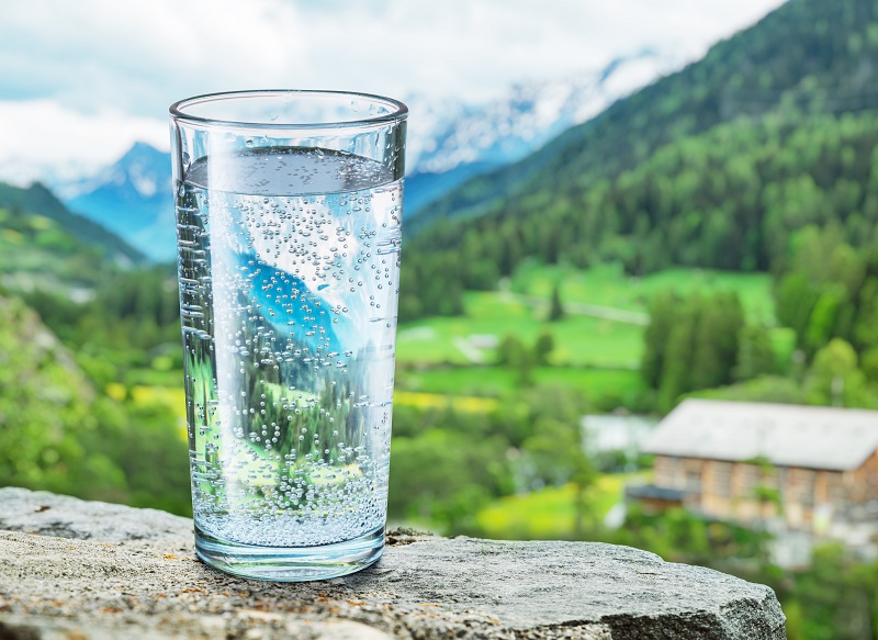Glass of water on the stone close-up. Blurred snow mountains tops and green forests at the background.