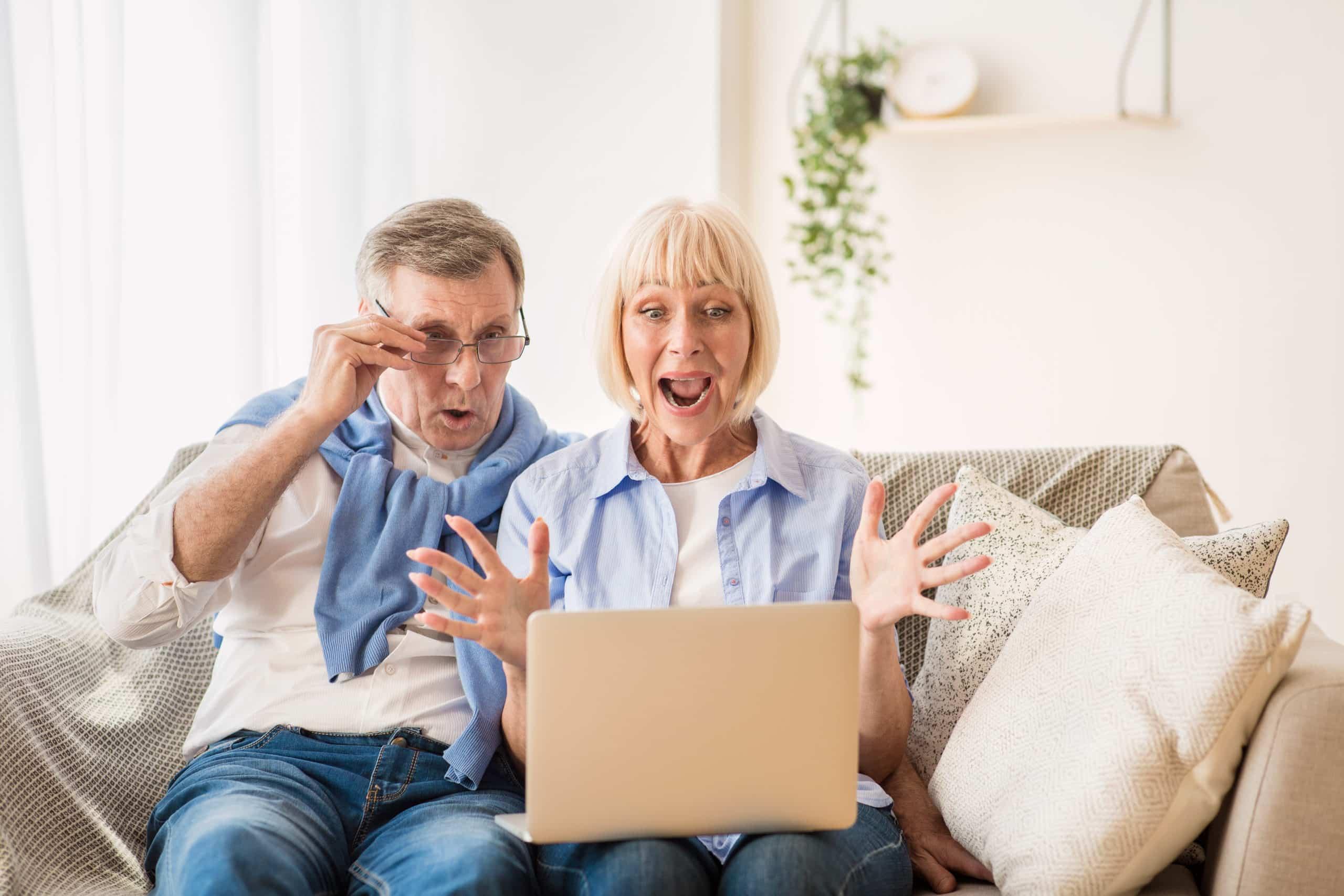 Surprised elder couple winning online auction bid